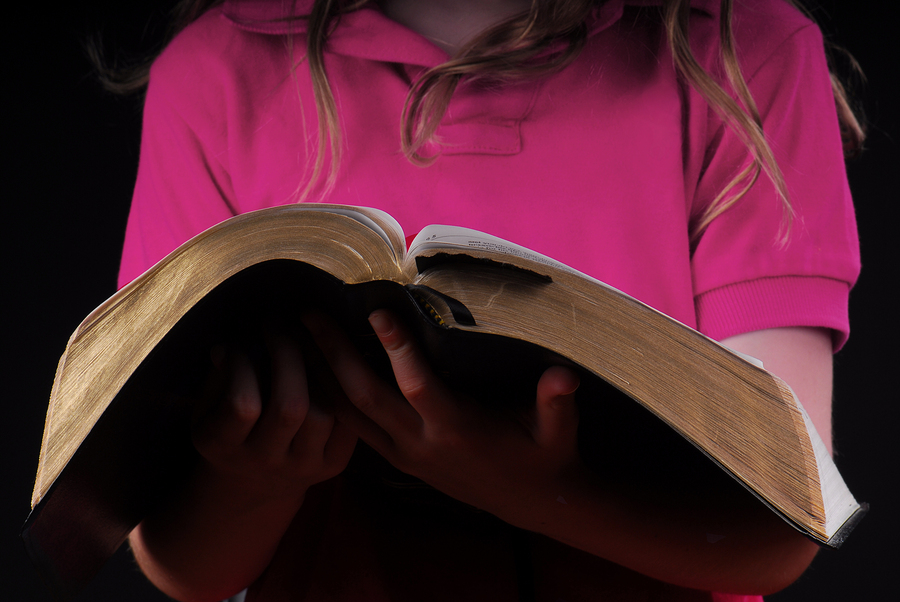 Young girl holding Bible in hands