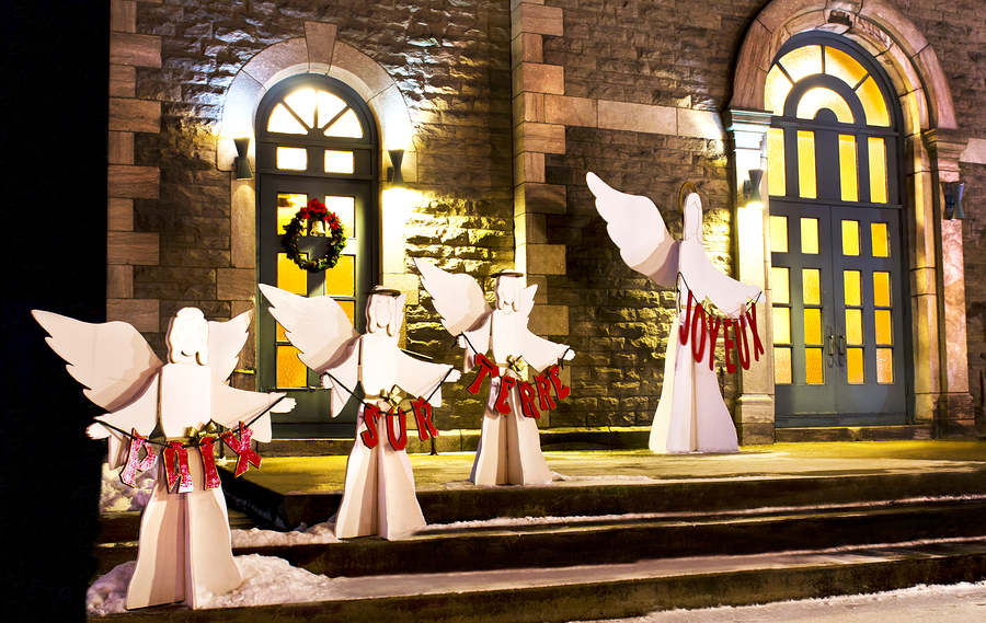 Christmas angels in front of church entrance in the evening.