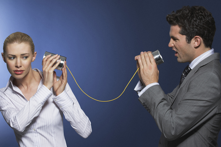 Businessman yelling at female colleague through tin can phone ag