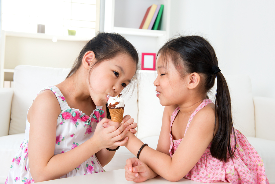 Eating ice cream. Asian girls sharing an ice cream. Beautiful ch