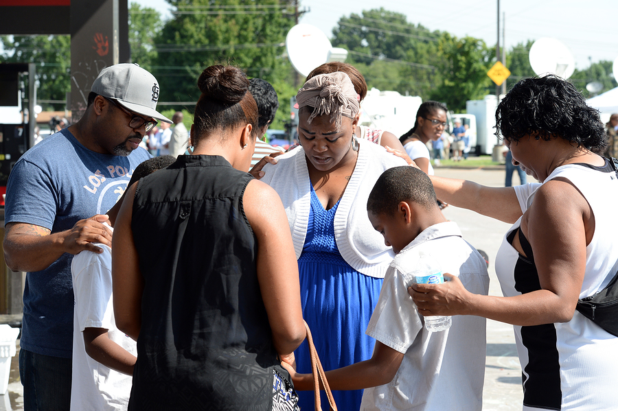 FERGUSON, MO/USA-  AUGUST 15, 2014: Group prays at the site of d